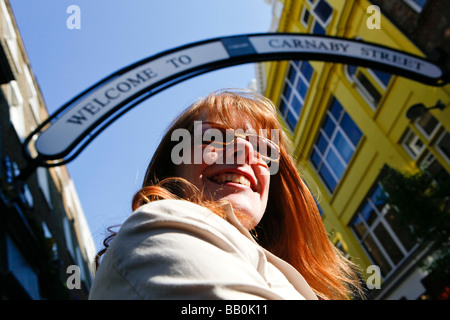 Frau mit roten Haaren auf der Carnaby Street London. - Stockfoto