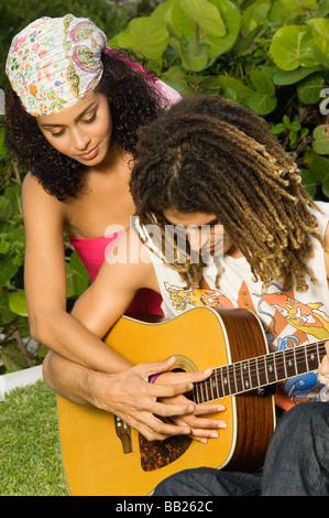 Mann einer Frau lehrt, wie man eine Gitarre zu spielen - Stockfoto
