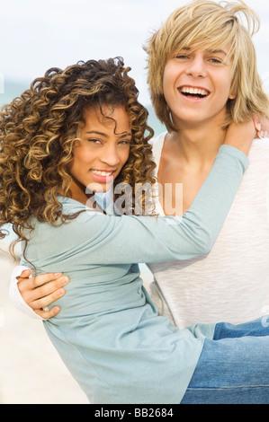 Teenager tragen eine Mädchen am Strand - Stockfoto