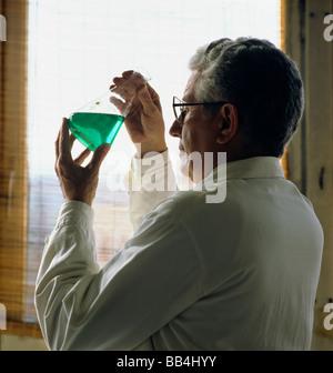 Biologe prüfen grüne Flüssigkeit in den Becher vor Fenster, Frankreich - Stockfoto