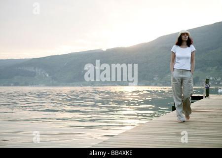 Frau zu Fuß auf einem Steg am See - Stockfoto