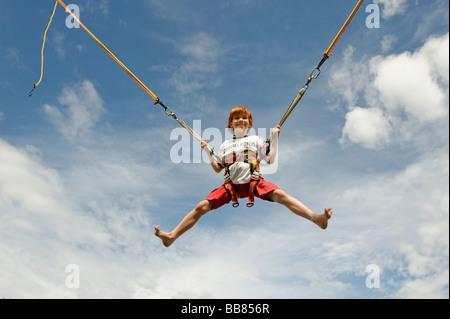 Junge auf einem Bungee-Trampolin springen und fliegen in der Luft - Stockfoto