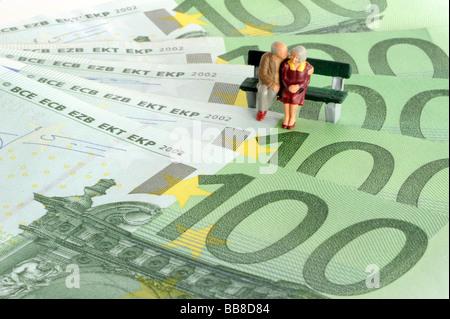 Miniaturfiguren Rentner sitzen auf einer Bank auf Euro-Banknoten, symbolisches Bild für Rente, Altersvorsorge - Stockfoto