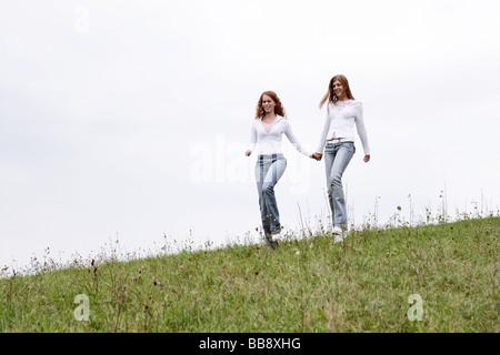 Zwei Jugendliche, die zu Fuß auf einem Feld - Stockfoto