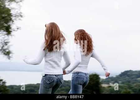 Zwei Jugendliche, die zu Fuß auf einem Feld mit Blick auf den See - Stockfoto