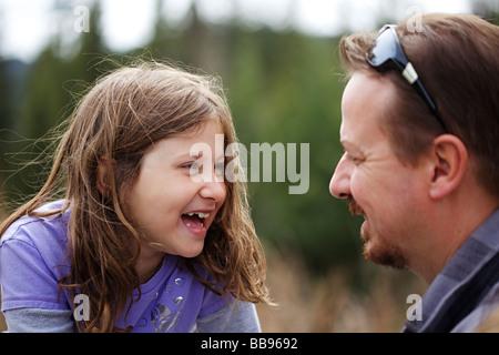 Fröhliches junges Mädchen mit ihrem Vater auf dem Spielplatz spielen - Stockfoto