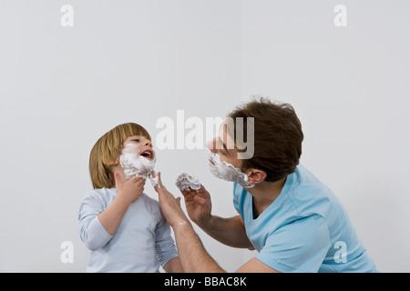 Ein Vater seinen jungen Sohn Rasierschaum zuweisen - Stockfoto