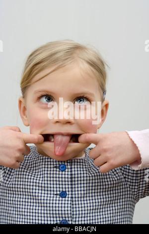 Ein kleines Mädchen, so dass ein Gesicht - Stockfoto