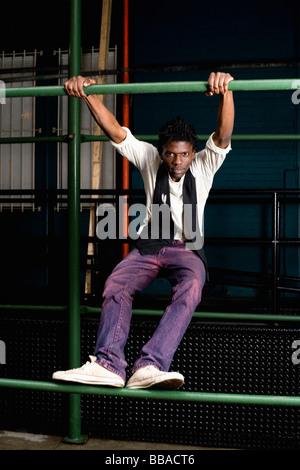 Ein junger Mann auf einer Metallstange halten - Stockfoto