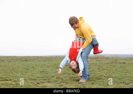 Ein Mann hält ein Junge auf dem Kopf stehend in einem park - Stockfoto