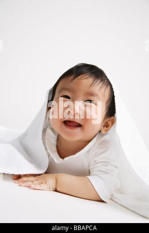 Baby Boy spähen aus unter Decke - Stockfoto