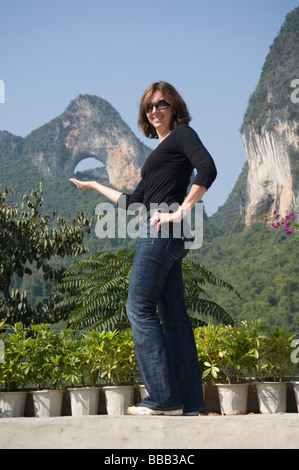 Moon Hill, Yangshuo, China; Frau posiert vor Berg - Stockfoto