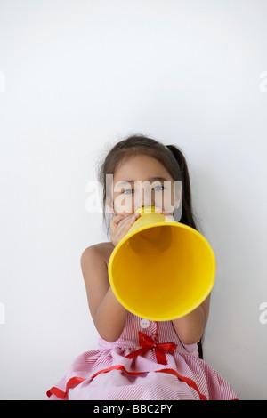 Ein junges Mädchen spielt mit einem gelben Kegel - Stockfoto