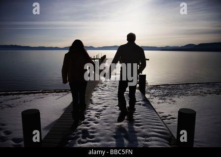 Paare, die auf verschneiten Pier bei Sonnenuntergang - Stockfoto