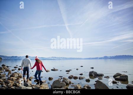 Paare, die auf Felsen in der Nähe von See - Stockfoto