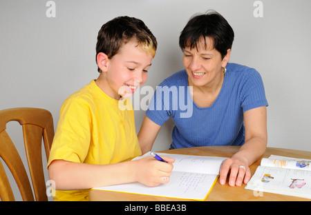 Boy Hausaufgaben für die Schule, Mutter hilft ihm, beide lachen - Stockfoto