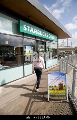 Ein junges Mädchen geht zu Starbucks, Cambridge, UK - Stockfoto