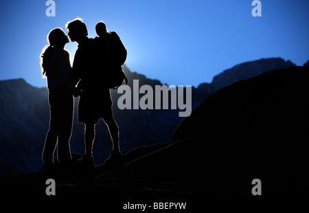 Junges Paar küssen in die untergehende Sonne während des Tragens Sohn auf Rücken, Sierra Nevada, Kalifornien - Stockfoto