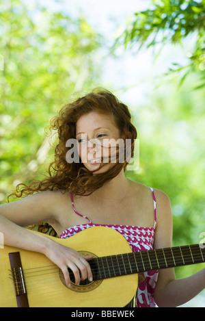 Junge Frau spielt akustische Gitarre im freien - Stockfoto