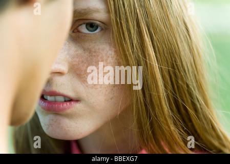 Junge Frau vor Mann starrte misstrauisch auf Kamera, beschnitten - Stockfoto