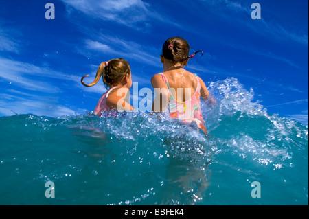 Zwei junge Mädchen spielen in den Wellen des Ozeans mit blauem Himmel. Dieses Bild hat viel Bewegungsunschärfe, - Stockfoto