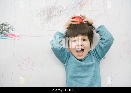 Ein Junge mit einem Apfel auf dem Kopf - Stockfoto