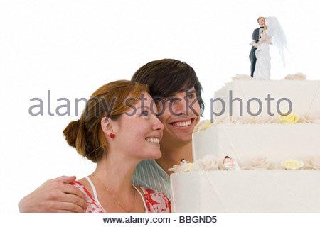 Junges Paar Blick auf Hochzeitstorte, lächelnd, Ausschneiden - Stockfoto