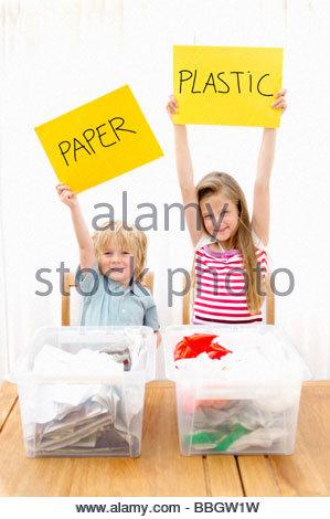 Jungen und Mädchen hält Papier und Kunststoffschild mit recycling Container Vordergrund, Den Haag, Niederlande - Stockfoto