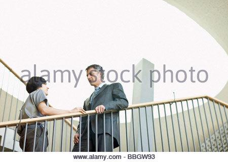 Geschäftsleuten stehen am oberen Treppe Diskussion - Stockfoto