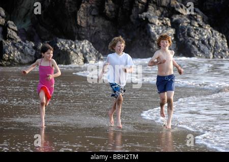 Drei glückliche Kinder im Urlaub entlang des Strandes in Woolacombe in Dorset - Stockfoto