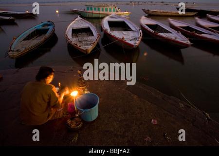 Varanasi, Uttar Pradesh, Indien; Mann, sitzend auf Felsen am Rande des Flusses - Stockfoto