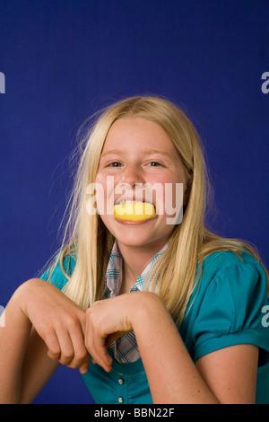 Portrait des dummen Jungen Mädchen 10-12 Jahre alten Holding Zitrone in den Zähnen, Mund, Studio shot out cut Kinder - Stockfoto