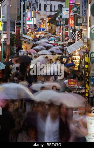 Shopper mit Sonnenschirmen an einem regnerischen Tag drängen Takeshita-Dori (Takeshita Street) in Harajuku, Tokyo, - Stockfoto