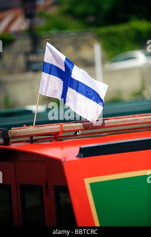 Finnische Flagge, die von einem Lastkahn - Stockfoto