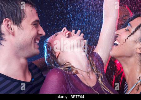 Eine Schar von Freunden, tanzen im Regen - Stockfoto