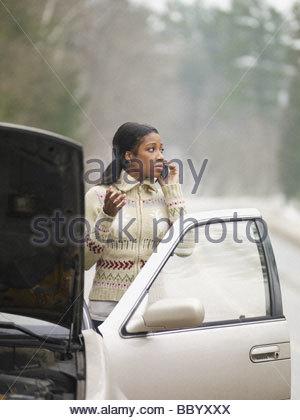 Afrikanische Frau mit Handy neben Auto mit Kapuze - Stockfoto