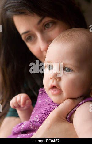 Mutter vier Monate altes Babymädchen halten und küssen ihren Kopf, Nahaufnahme - Stockfoto