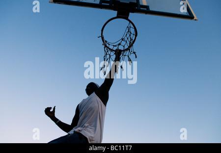 Junge schwarze Mann hängen von einem Basketballkorb mit zerrissenen Net - Stockfoto