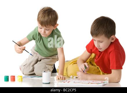 zwei jungen zeichnen mit Farben am Boden isoliert auf weiss - Stockfoto