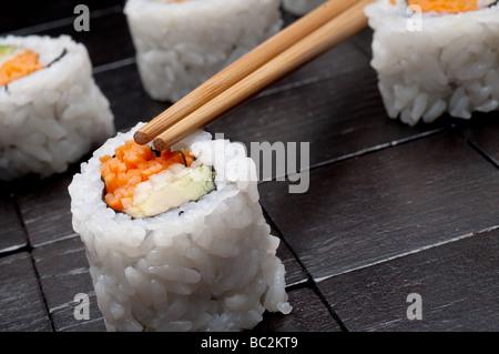eine geneigte horizontale flachen Fokus Makro Sushi mit Copsticks auf einem schwarzen Hintergrund aus Holz - Stockfoto