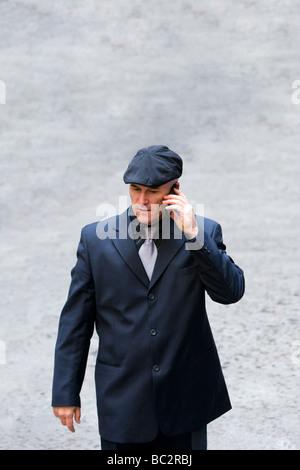 Glatzkopf in seiner späten 40 trägt einen dunklen Anzug und Kappe auf einem Handy gesehen. - Stockfoto