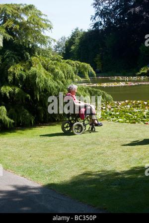 Alte Dame im Rollstuhl an der formalen Gärten von burnby Hall Nr Pocklington East Yorkshire, UK GB England suchen - Stockfoto