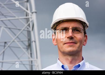 Lächelnder Ingenieur vor Konstruktion aus Stahl - Stockfoto