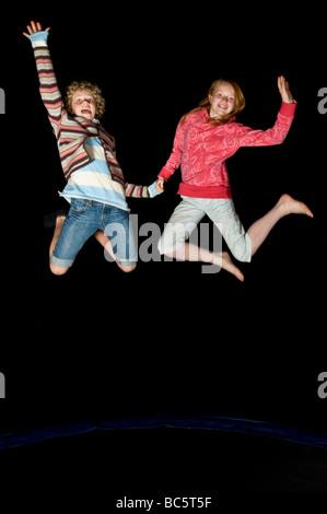 """2 junge Teenager-Freundinnen springen auf einem Trampolin beim Lachen in der Nacht auf einem Geburtstag """"Sleepover"""". - Stockfoto"""