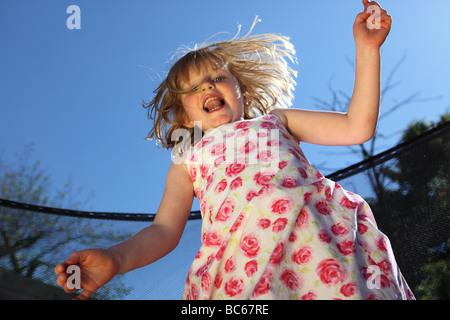 ein junges Mädchen an einem heißen Sommertag auf einem Trampolin springen - Stockfoto