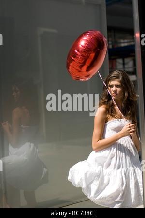 Frau mit roten Ballon in der Innenstadt - Stockfoto