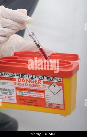 """Krankenschwester, Entsorgung von Blut gefüllte Spritze im Krankenhaus """"Sharps"""" Entsorgungsbehälter - Stockfoto"""
