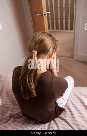 Junges Mädchen sitzt auf ihrem mit dem Rücken zur Kamera, Bettkopf besorgt bei geöffneter Tür. - Stockfoto