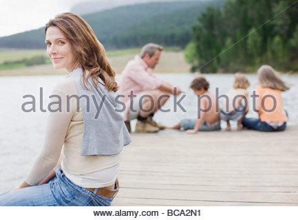 Familie sitzt am Pier von See - Stockfoto