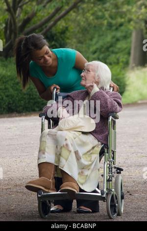 junge Frau, die ältere Dame im Rollstuhl schieben - Stockfoto